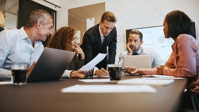 Diverse businesspeople working together around an office boardroom table