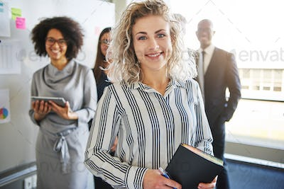 Smiling young businesswoman leading a team of diverse colleagues