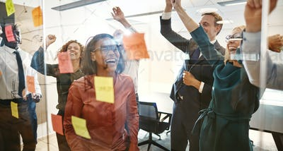 Cheering businesspeople celebrating success after brainstorming together in an office