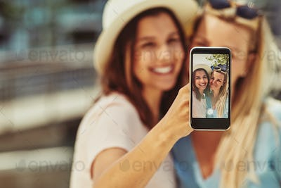 Two young female friends taking selfies together outside in summer