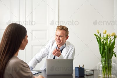 Cheerful beautician man consulting woman at laptop in salon