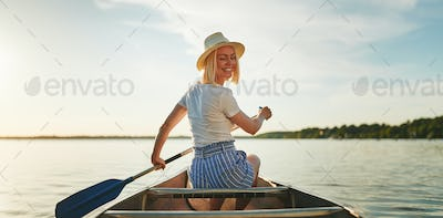 Smiling woman canoeing on a still lake in the summer