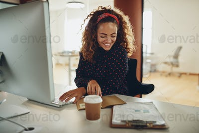 Smiling young businesswoman working at her desk in an office