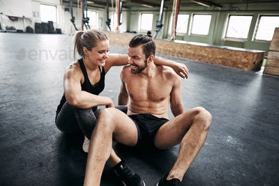 Affectionate couple relaxing together in a gym after working out
