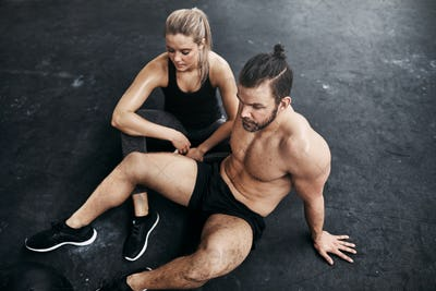 Two people resting together on a gym floor after exercising