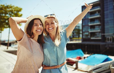 Two laughing female friends having fun walking together in summer