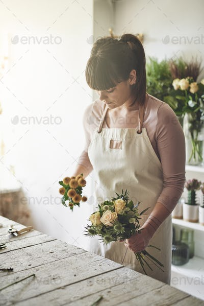 Florist making flower arrangements at a bench in her shop