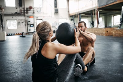 Two people exercising with a medicine ball at the gym
