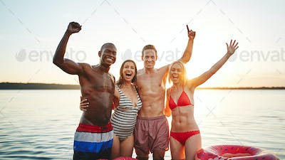 Smiling group of friends having fun in a lake at sunset