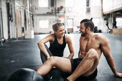 Two people sitting on a gym floor after working out