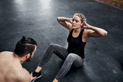Fit young woman doing crunches with a gym partner