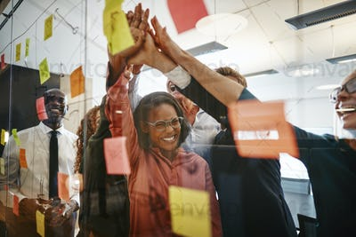 Excited businesspeople high fiving after an office brainstorming session