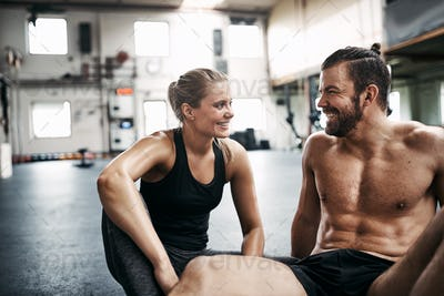 Smiling young couple taking a break from working out together