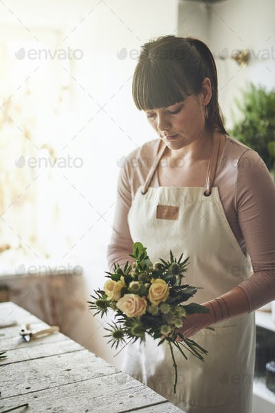 Female florist standing in her flower shop making a bouquet