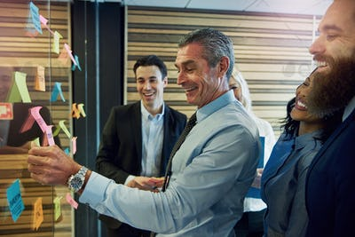 Smiling businesspeople with sticky notes