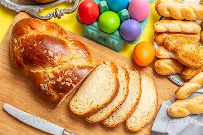 Easter eggs and tsoureki braid, greek easter sweet bread, on wood
