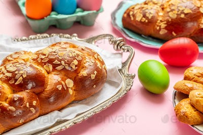 Easter eggs and tsoureki braid, greek easter sweet bread, on pink color background