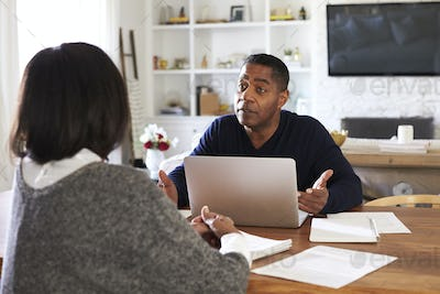 Millennial man with laptop computer giving financial advice to a woman