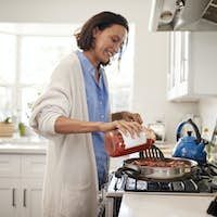 Young mixed race adult woman standing in the kitchen cooking on the hob