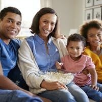 Young mixed race family sitting together on the sofa in their living room