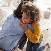 Pre-teen girl hugging her mother sitting on sofa in the living room, elevated, back view