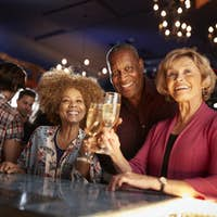 Portrait Of Senior Friends Drinking In Bar Together