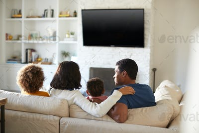 Back view of young family sitting on the sofa and watching TV together
