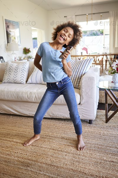 Pre-teen black girl singing and dancing in the living room using smartphone