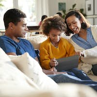 Parents and their daughte in the living room using a tablet computer together, selective focus