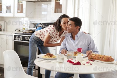 Young adult woman kissing her partner, sitting at the table in their kitchen