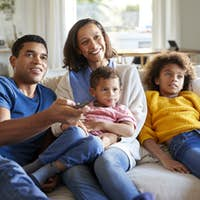 Front view of young family sitting together on the sofa in their living room watching TV