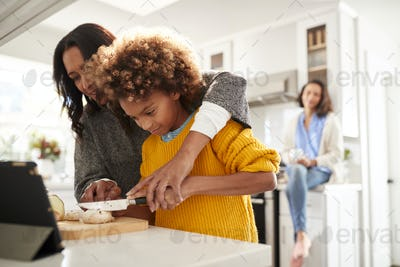 Grandmother helping her granddaughter prepare food in the kitchen