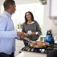 Man standing in the kitchen cooking and talking to his partner, standing beside him