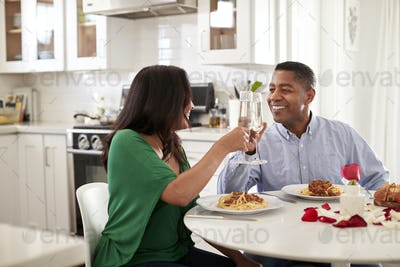 Middle aged mixed race couple making a toast over a romantic meal in their kitchen, close up