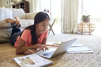 Teenage girl lying on the floor doing her homework using a laptop computer