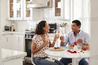 Young couple sitting at the table in their kitchen making a toast whilst eating a meal