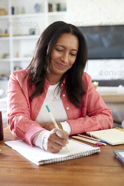 Smiling mixed race retired woman sitting at a table writing in her dining room, close up, vertical