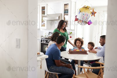 Pre teen girl sitting at the kitchen table with her three generation family celebrating her birthday