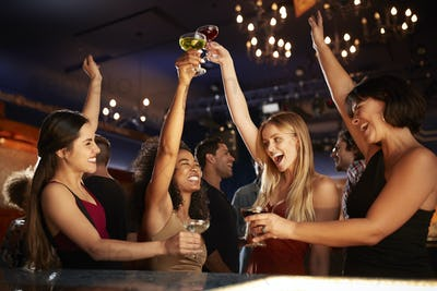 Group Of Female Friends Celebrating In Cocktail Bar Together