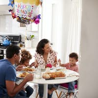 Young mixed race family having a birthday meal together at the table in their kitchen