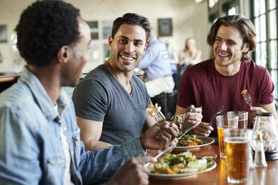 Group Of Male Friends Enjoying Meal In Restaurant Together