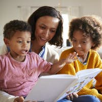 Excited toddler boy sitting on his mother's knee reading a book with his sister