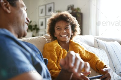 Close up of father and daughter sitting on sofa in the living room looking at each other,  smiling