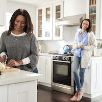Middle aged woman standing at a worktop in the kitchen preparing food with adult daughter