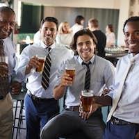 Portrait Of Businessmen Meeting For After Works Drinks In Bar