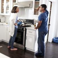 Young mixed race couple standing in the kitchen talking, full length