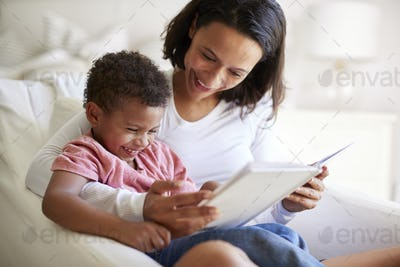 Close up of mixed race young adult mother sitting in an armchair reading a book with her young son