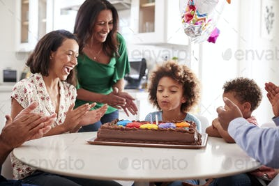 Giirl blowing out the candles on birthday cake with family