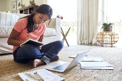 Teenage girl doing her homework sitting on floor in the living room, low angle, close up