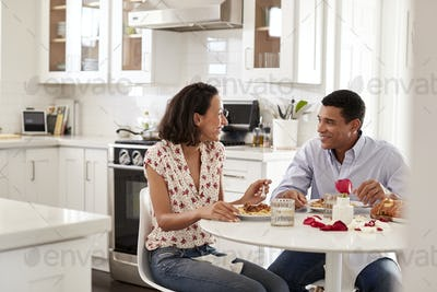 Young couple sitting at the table in their kitchen eating a romantic meal together, selective focus